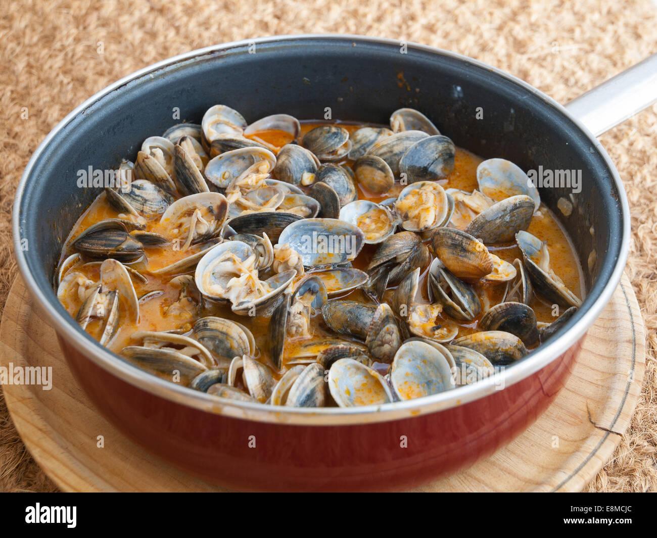 """Muscheln in dem Rezept """"Almejas a la Marinera"""" Hintergrund in einer Pfanne gekocht Stockbild"""