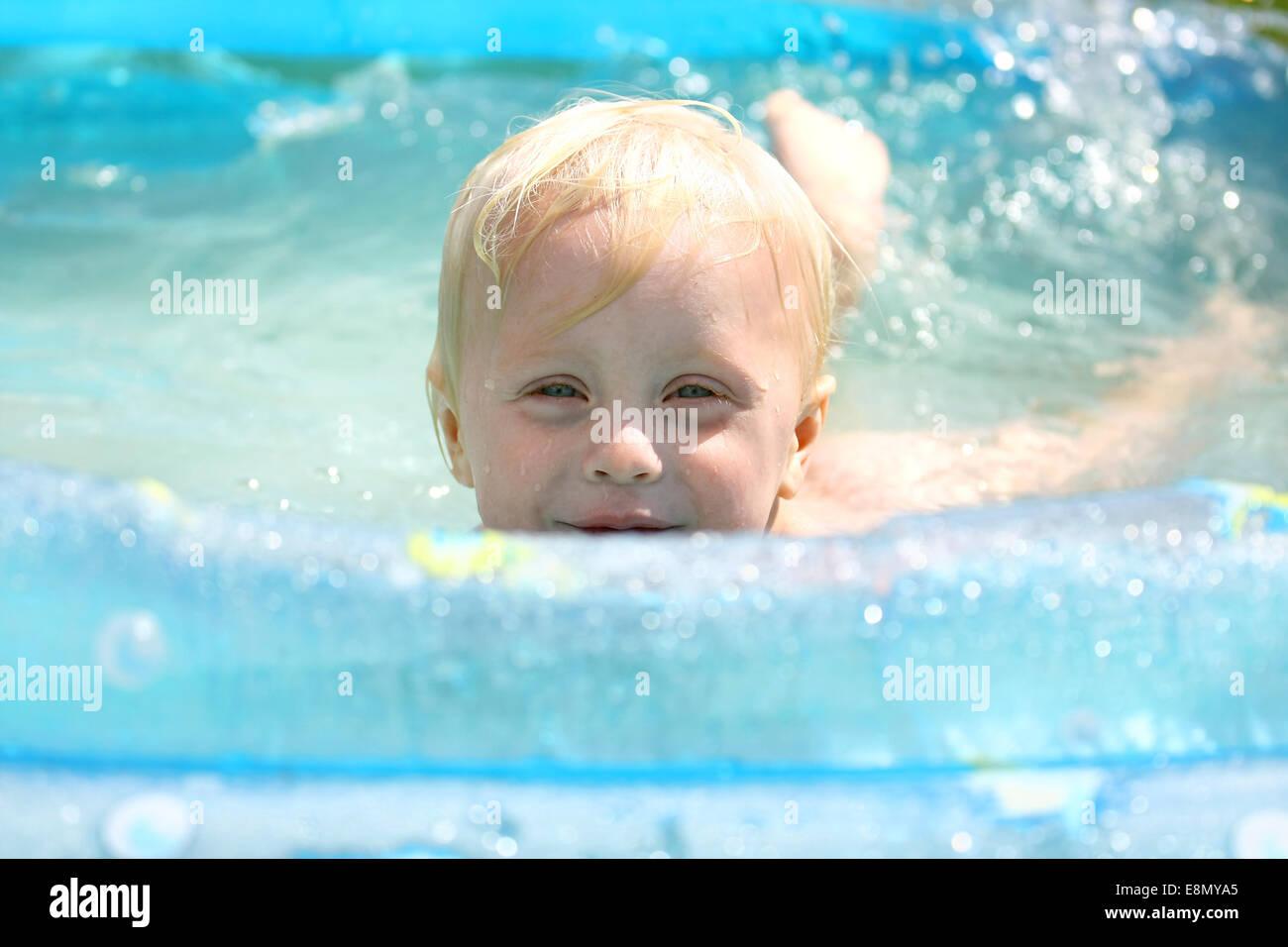 Ein glückliches Baby junge ist über den Rand eines Schwimmbades spähen, als er an einem Sommertag im Wasser spielt. Stockfoto
