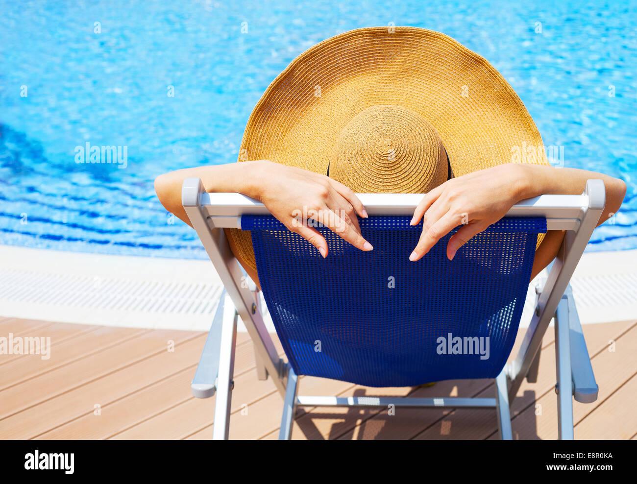 Schöne junge Frau mit Hut auf Liegestuhl am Swimmingpool liegen ...