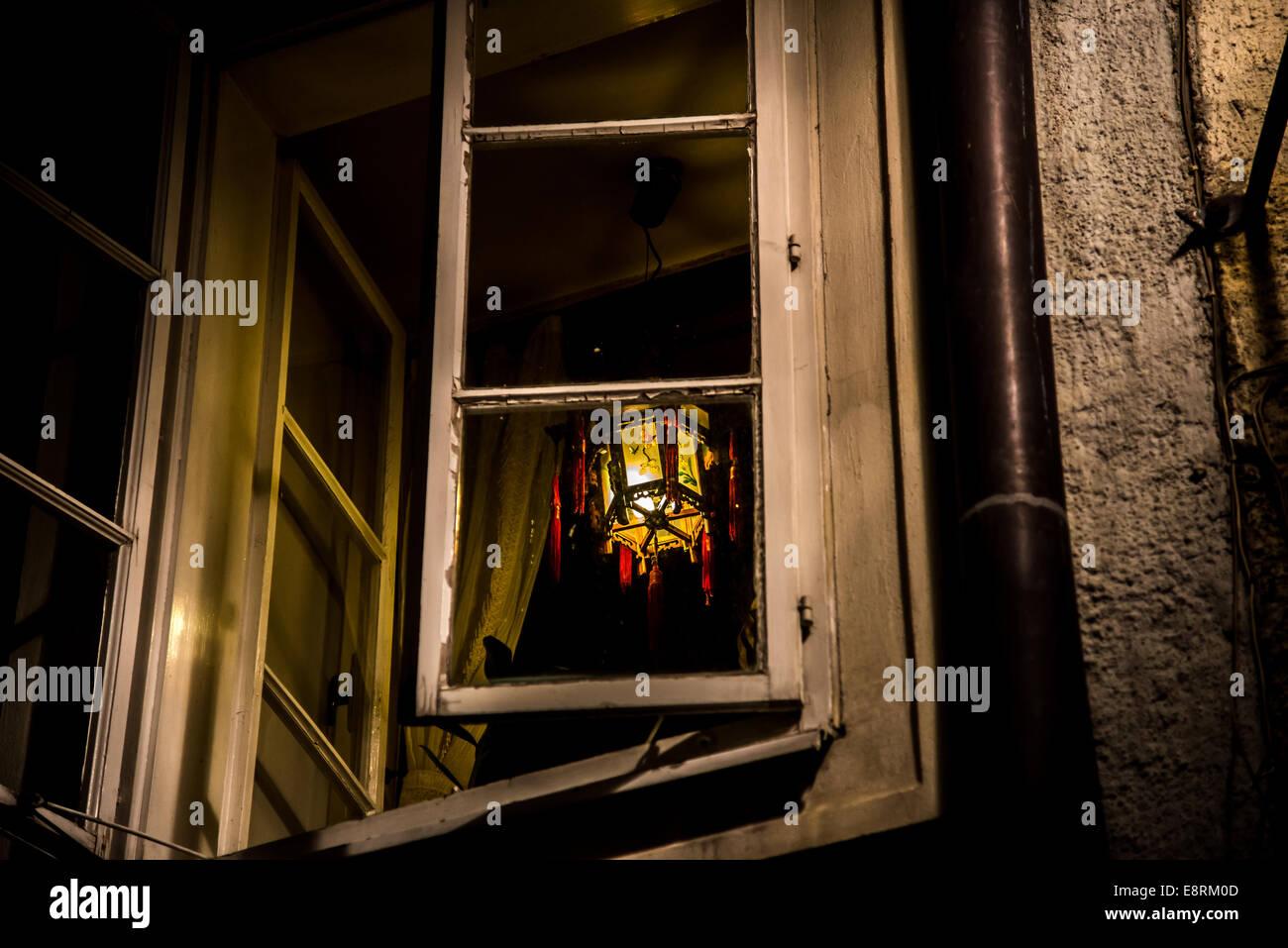 Eine reich verzierte Lampe hängt in einem geöffneten Fenster in einer warmen Nacht. Stockbild