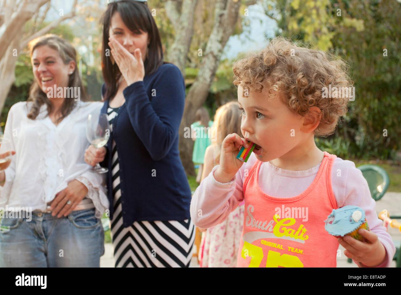 Junges Mädchen essen ihre Tasse Kuchen auf einer Party. Stockfoto