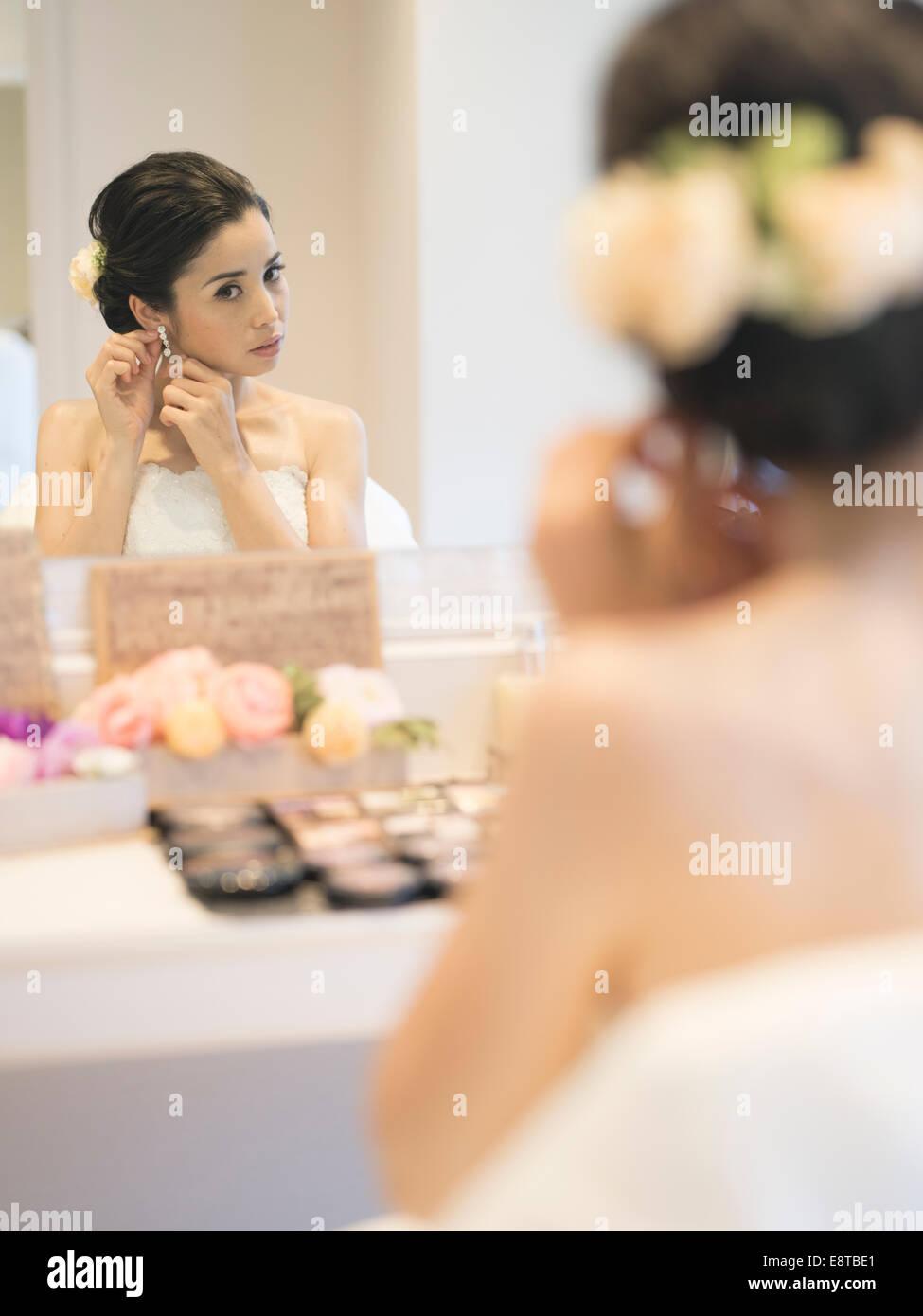 Gemischte Rassen, legt asiatischen / American Braut im weißen Hochzeitskleid auf Make-up und Ohrringe vor Hochzeit Stockbild