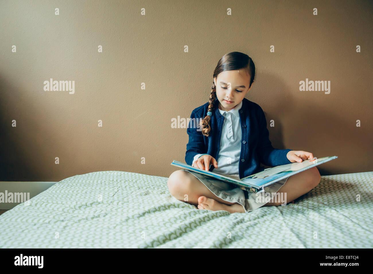 Gemischte Rassen Mädchen Lesebuch auf Bett Stockfoto