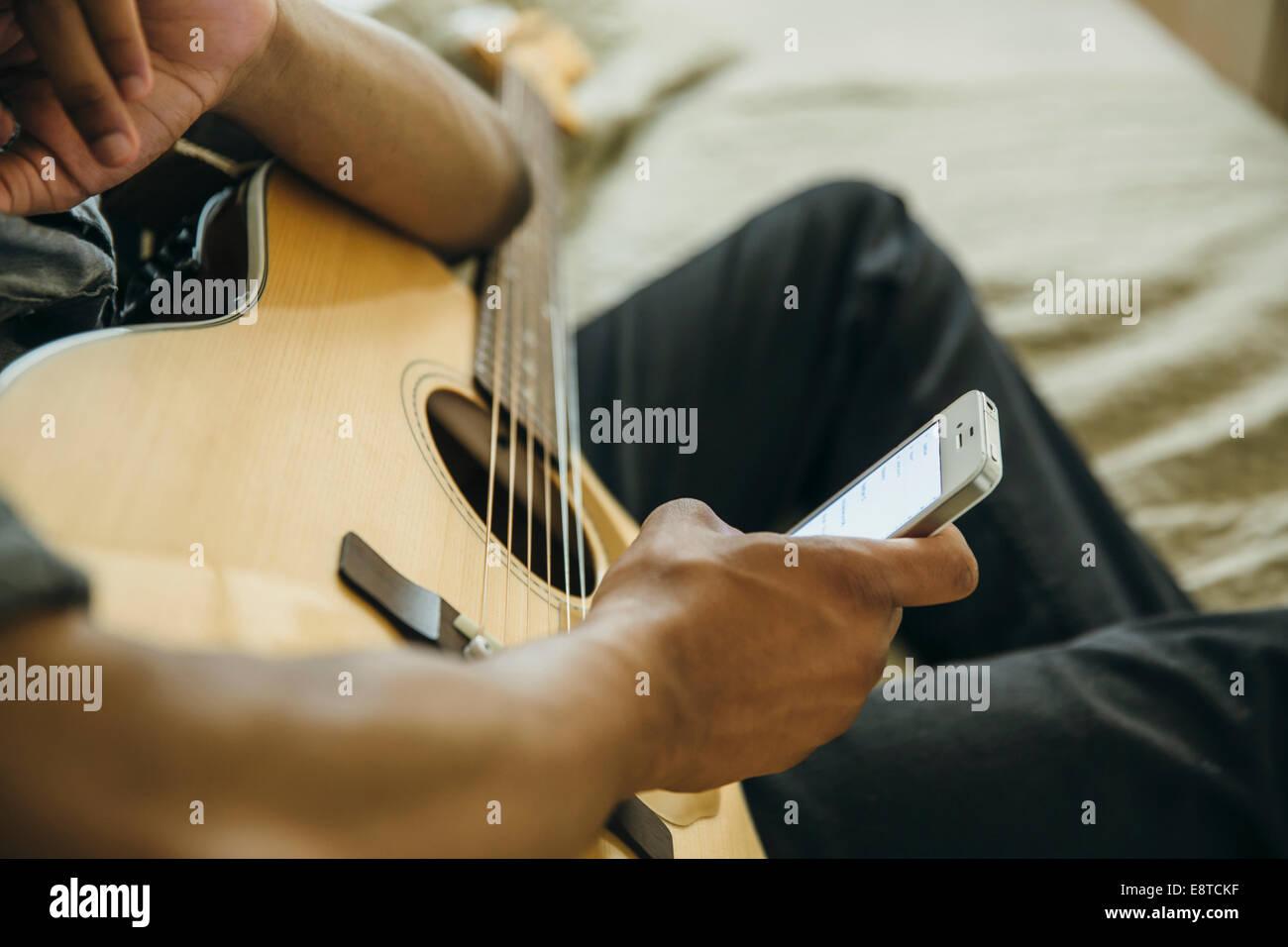 Gemischte Rassen junge mit Gitarre mit Handy Stockfoto