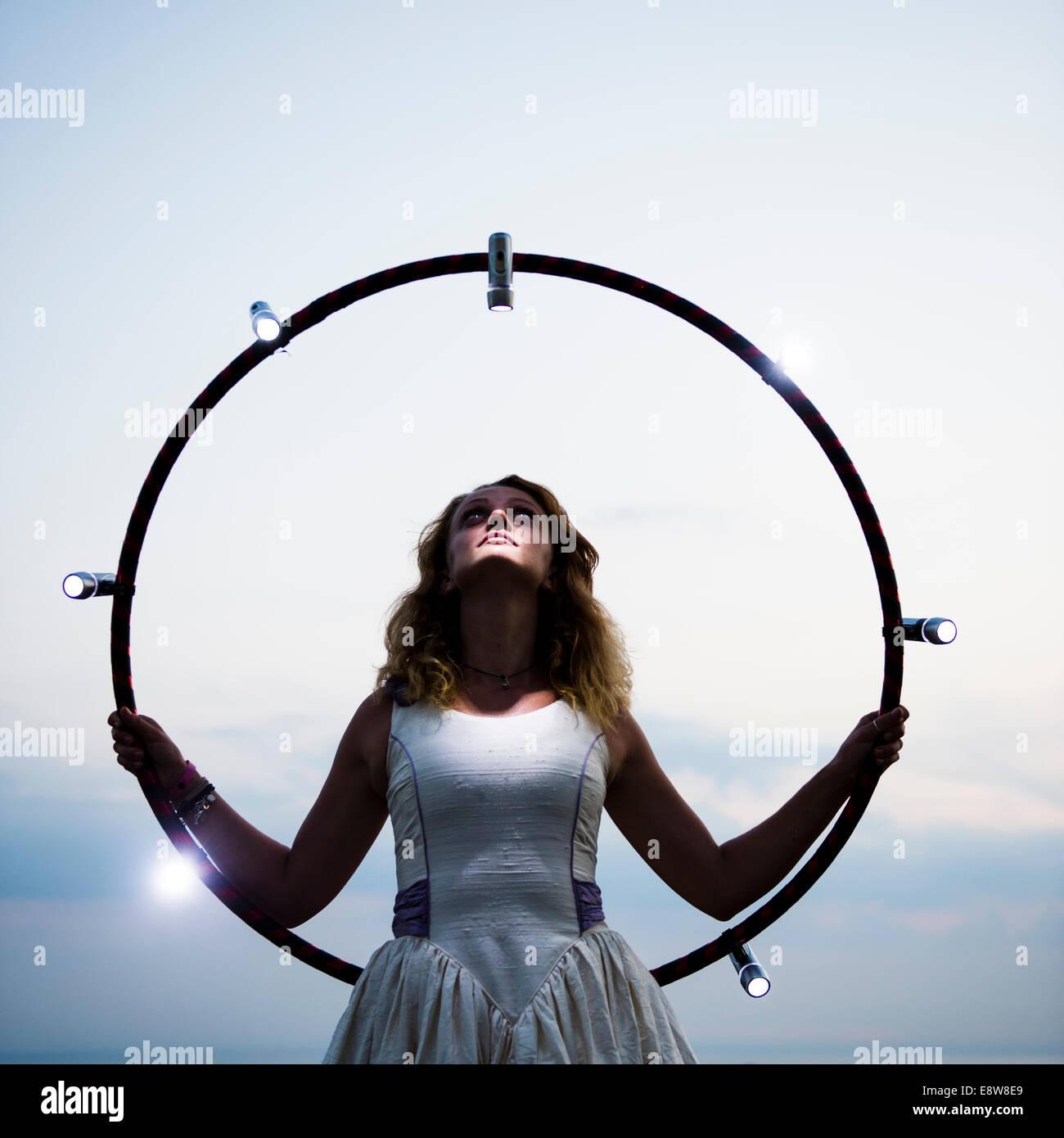Eine Frau in einem Brautkleid hält einen Hula-Hoop-Reifen mit Lichtern Stockbild