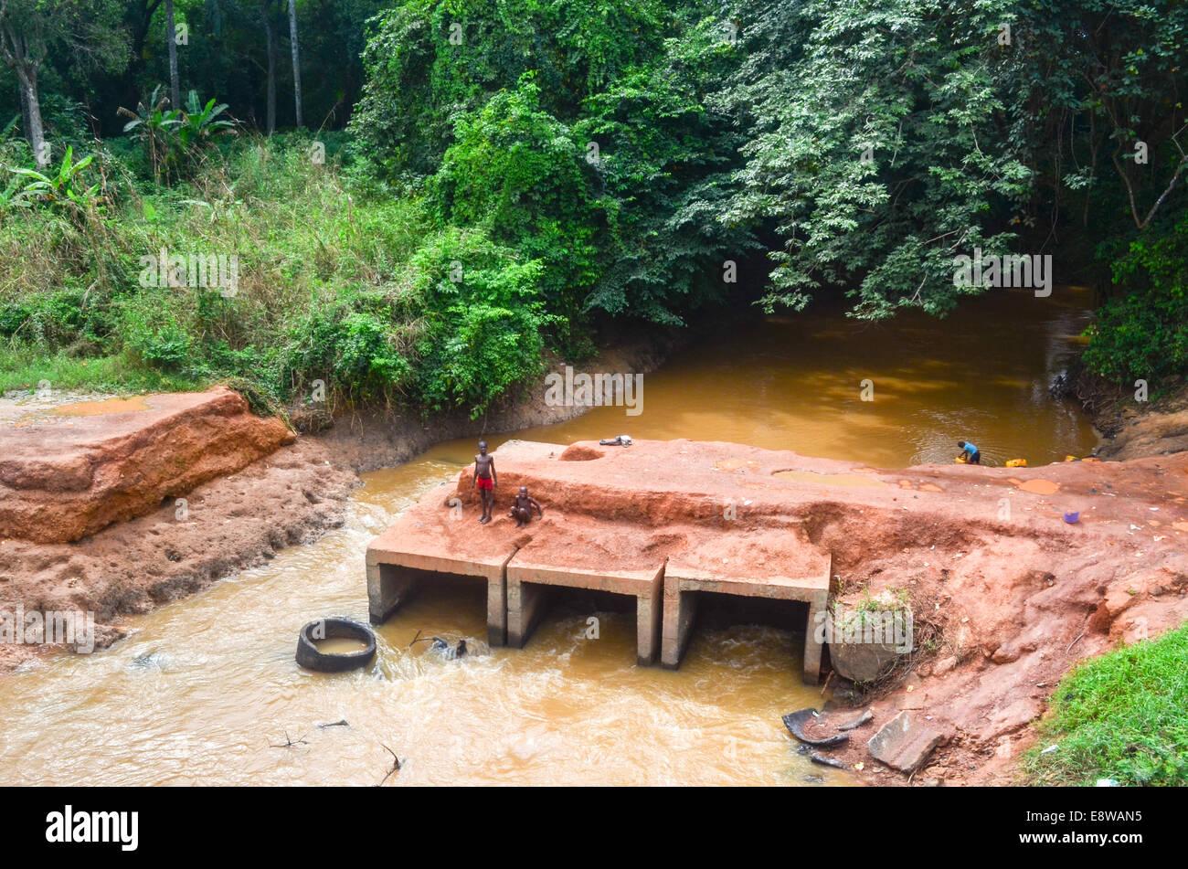 Schlechte Infrastruktur in Nigeria, Feldwege, Überschwemmungen und Kinder spielen mit unfertigen Brücken Stockbild