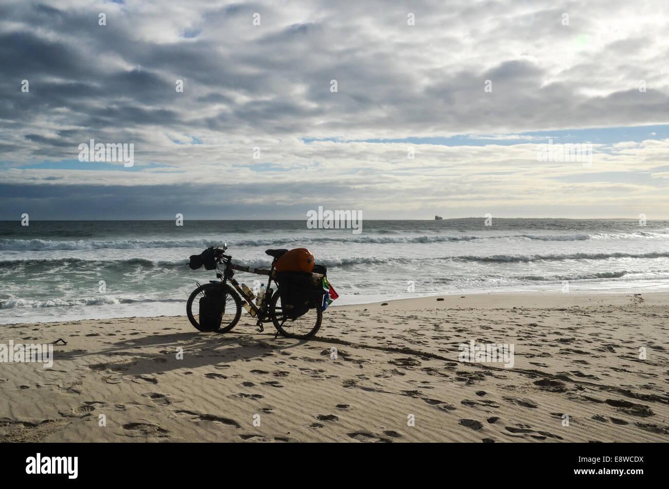 Zyklus auf Tournee in Afrika, ein Tourenrad am Strand in Cape Town, South Africa, mit bewölktem Himmel, Robben Island Stockfoto