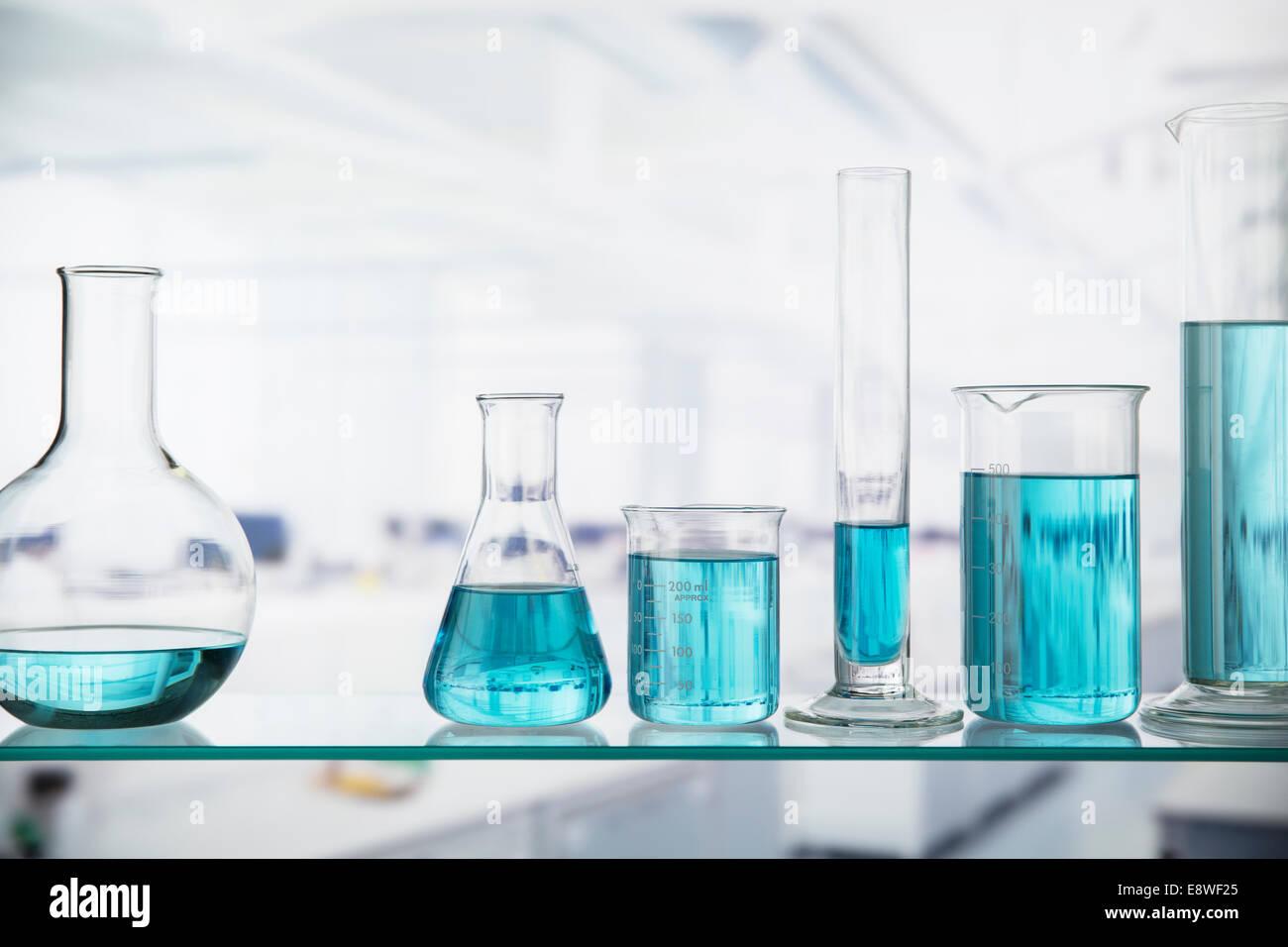 Nahaufnahme von Bechern mit Lösung auf Regal im Labor Stockfoto