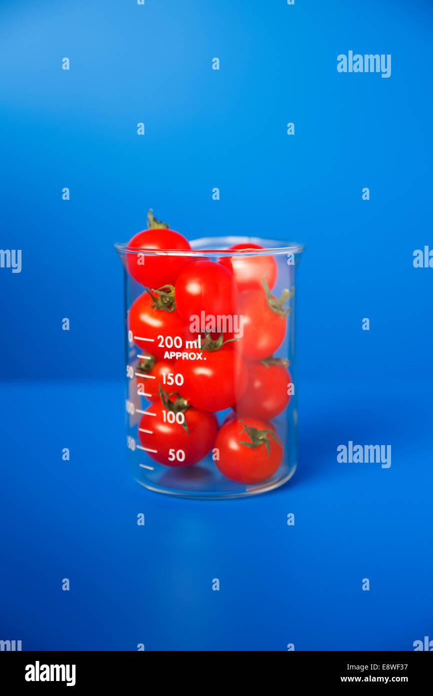 Becher mit kleinen Tomaten auf blauen Schalter Stockbild