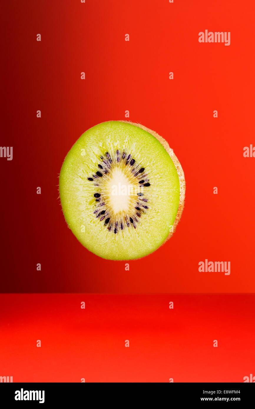 Kiwi-Scheibe auf roten Theke Stockbild