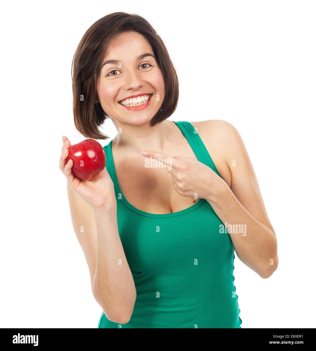 Schöne junge Frau hält und zeigt einen roten Apfel, isoliert auf weiss Stockbild