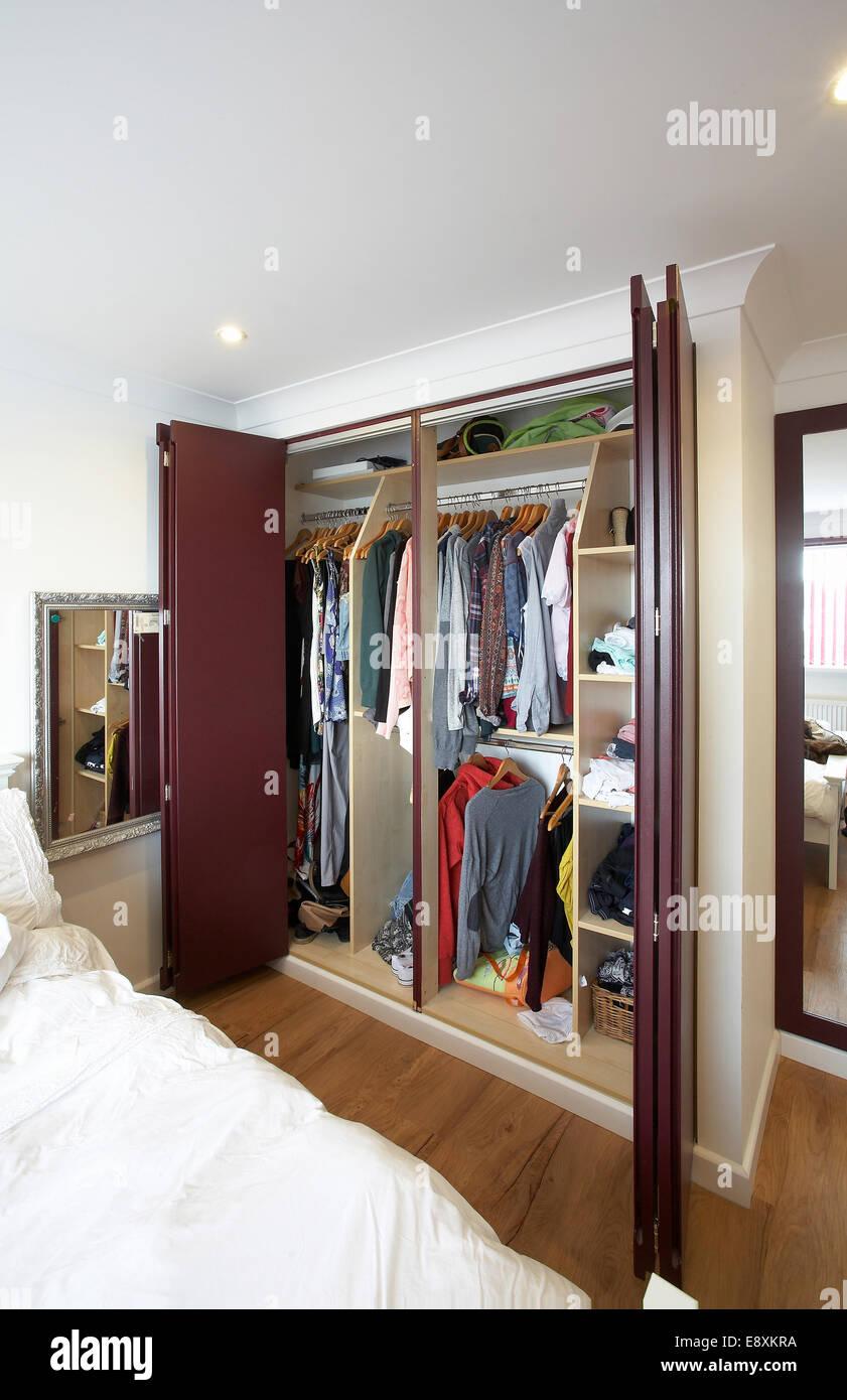Ein offener Kleiderschrank mit Falttüren in einem ...