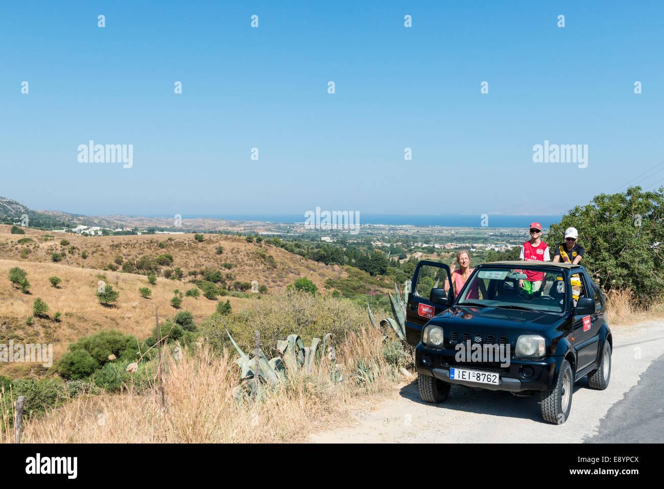 Mutter mit zwei Kindern fahren in einem offenen Jeep in die Berge zu Pili, Kos, Griechenland Stockbild