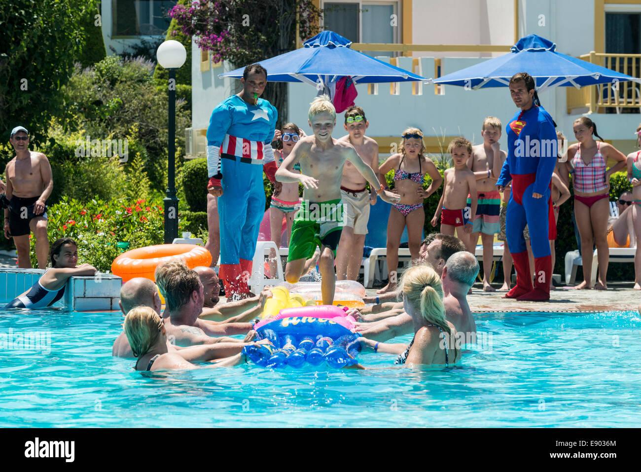 Urlaub-Entertainer und Kinder spielen eine Spiel in einem Schwimmbad, Mastichari, Kos, Griechenland Stockfoto