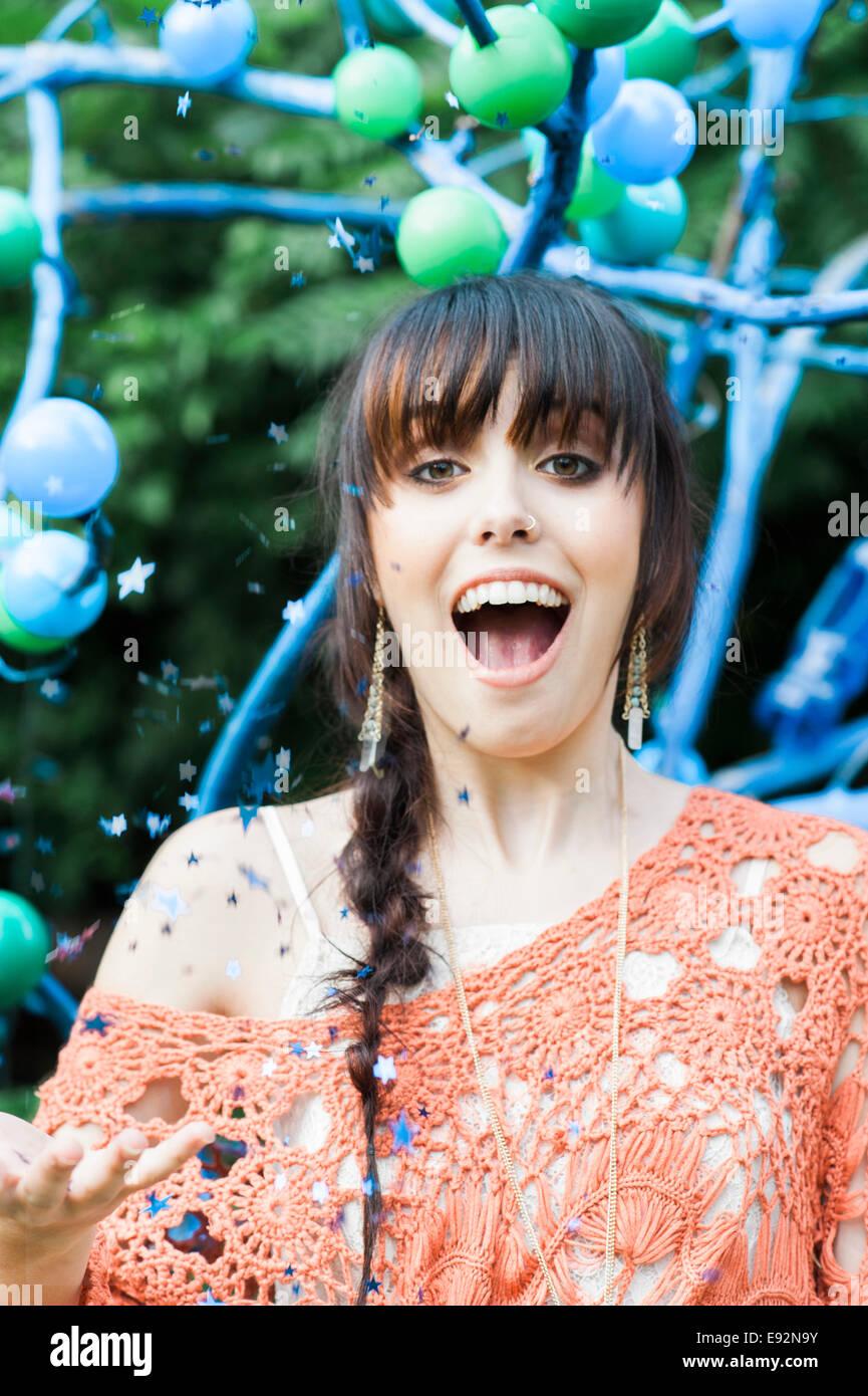 Lächelnde junge Frau mit Sterne Konfetti in die Luft Stockfoto