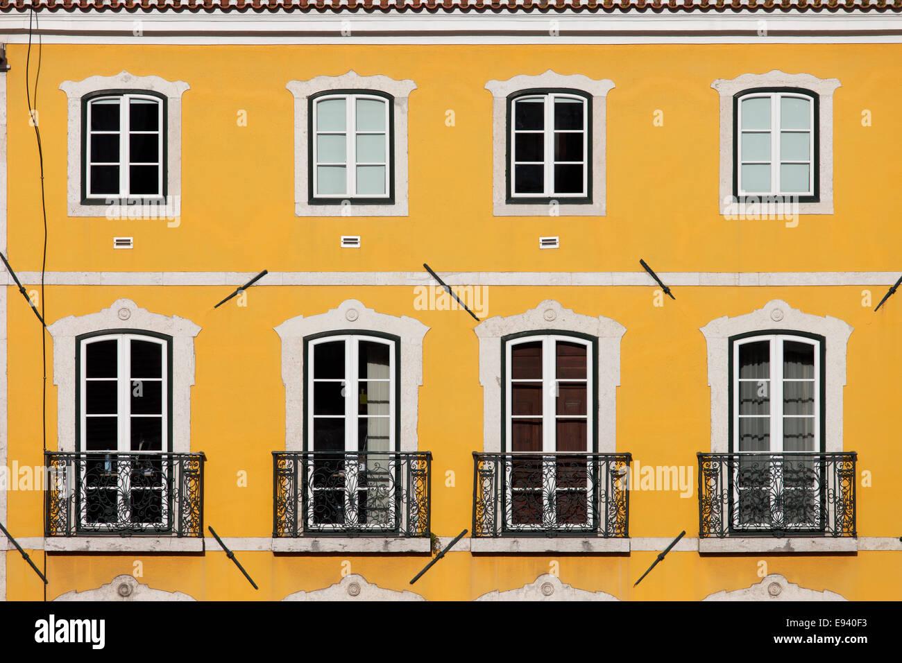 Traditionelles Haus mit gelber Fassade und große Fenster mit ...