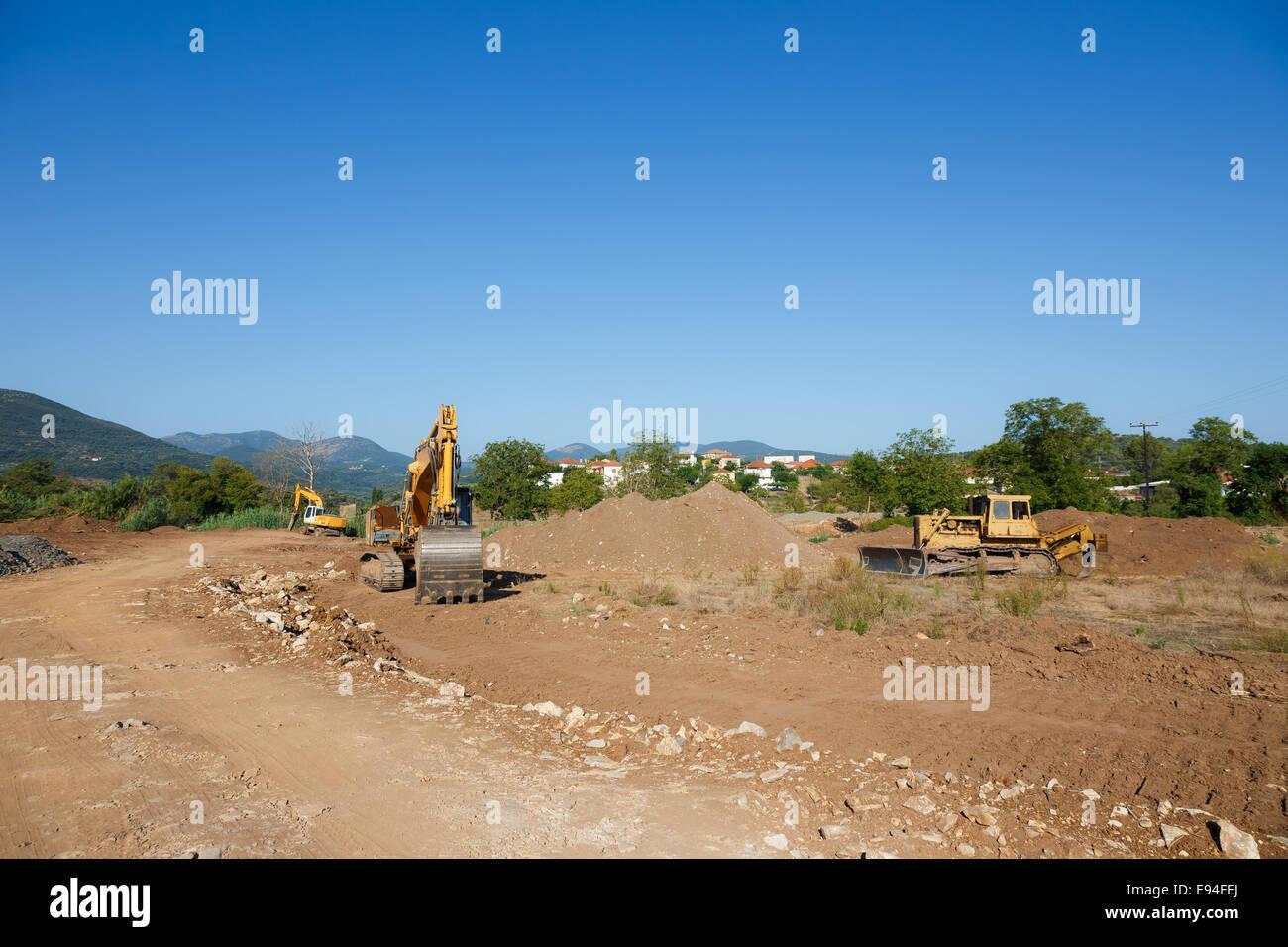Große Bagger auf neue Baustelle vor blauem Himmel Stockbild