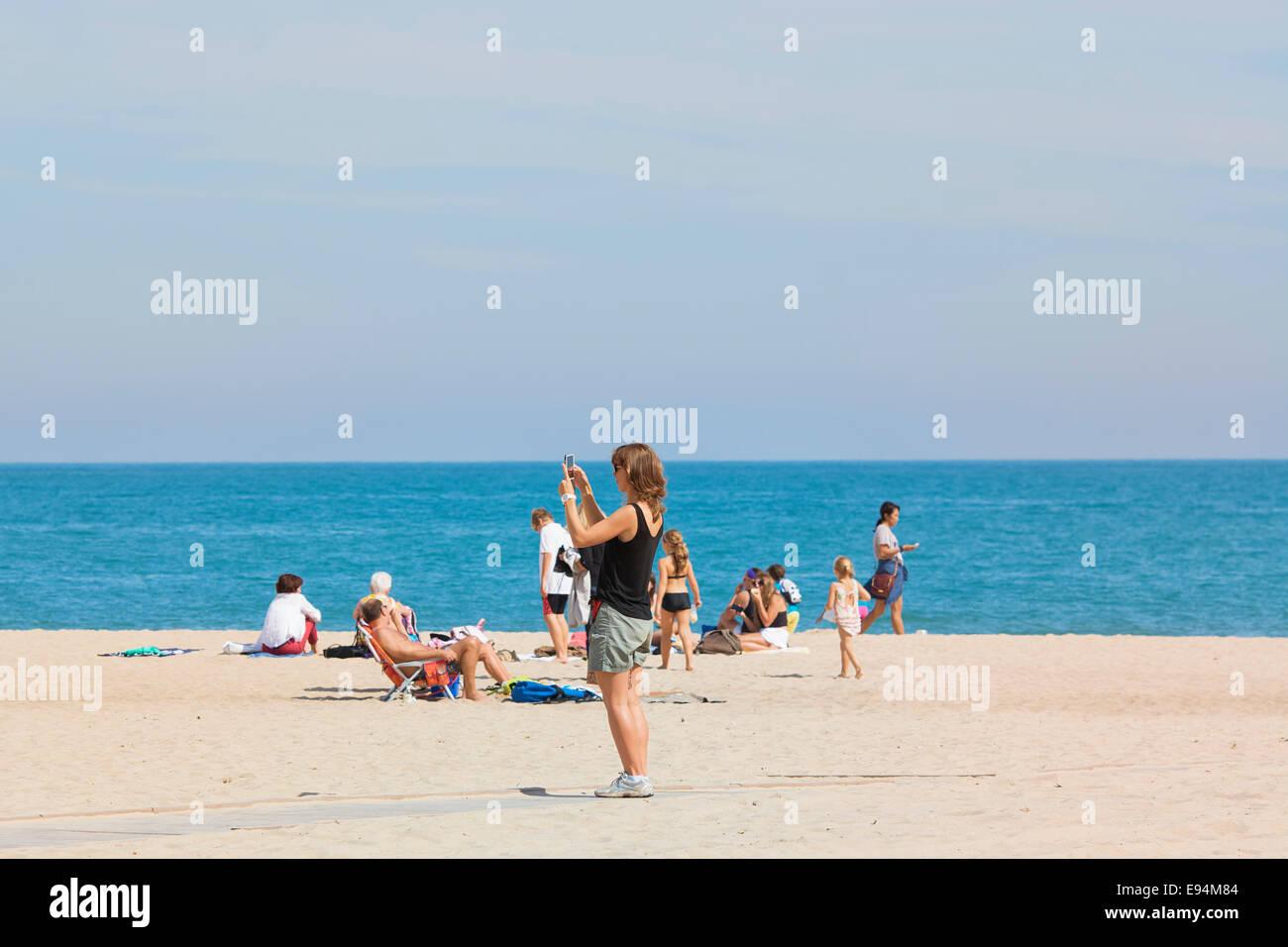 Frau am Strand mit Handy, fotografieren Stockfoto