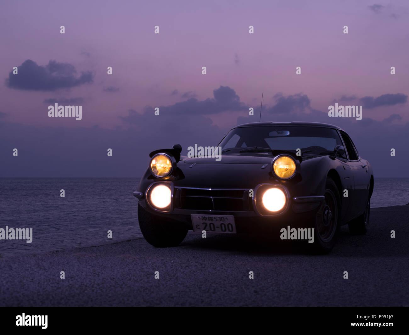 RHD Toyota 2000GT Sportwagen bei Sonnenuntergang in Okinawa, Japan. Extrem seltene klassische ikonische japanische Stockbild
