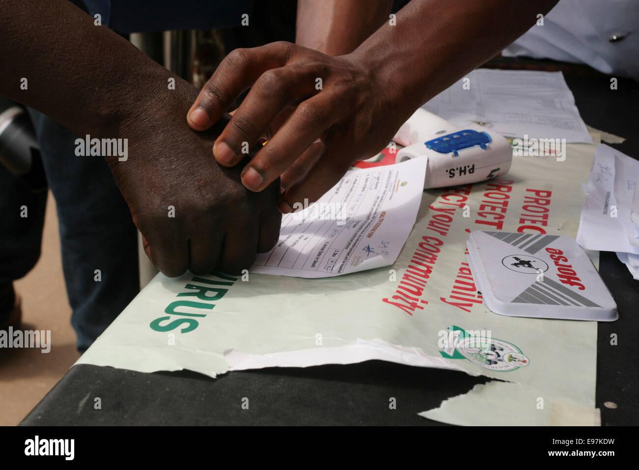 Health Officer hilft ein Analphabet, Daumen drucken Sie ein Dokument im Rahmen des Screenings für Ebola-Virus Stockbild