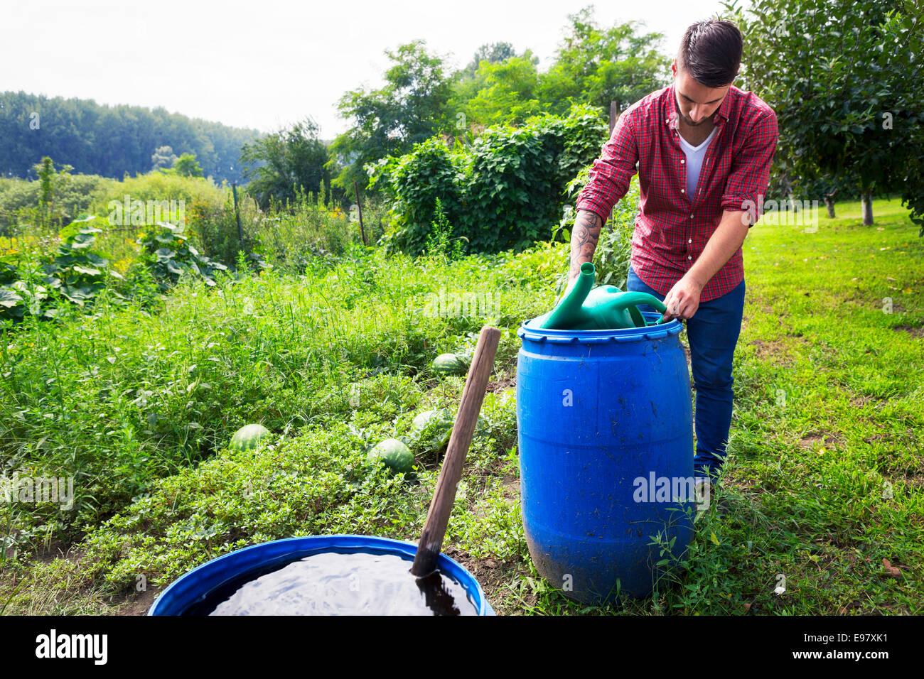 Junger Mann Füllung Gießkanne Barrel Stockbild