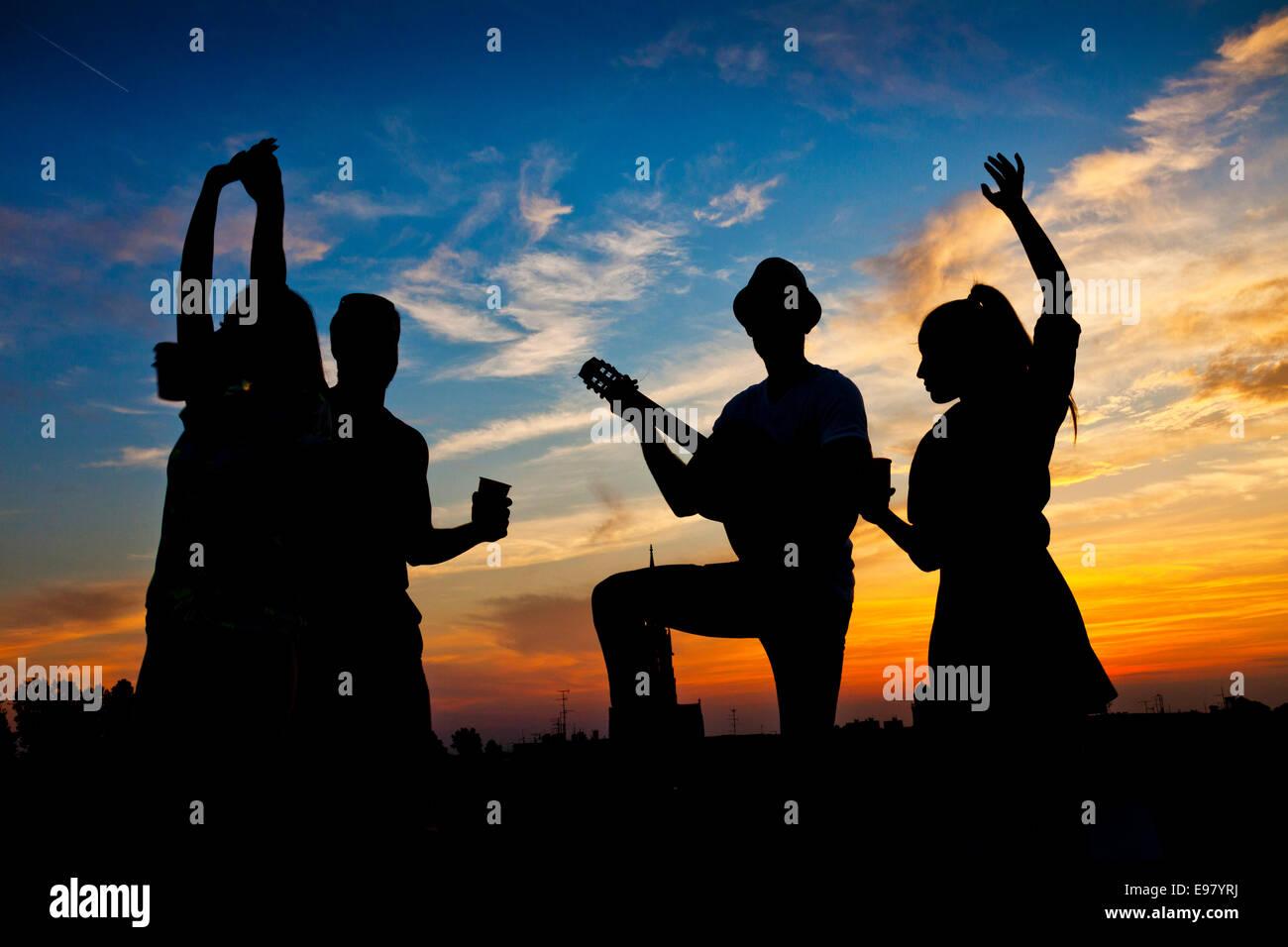 Junge Menschen tanzen und Spaß bei Sonnenuntergang Stockbild