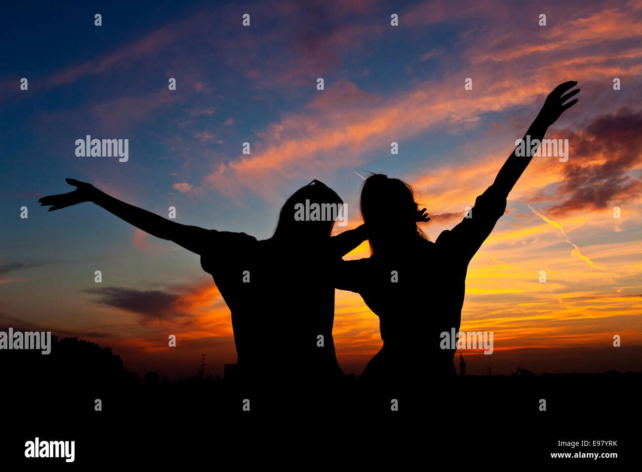 Junge Frauen mit erhobenen Armen tanzen bei Sonnenuntergang Stockbild