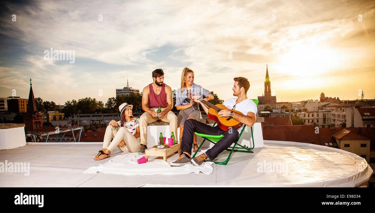 Junge Partypeople Gitarre Musikhören auf dem Dach Stockbild