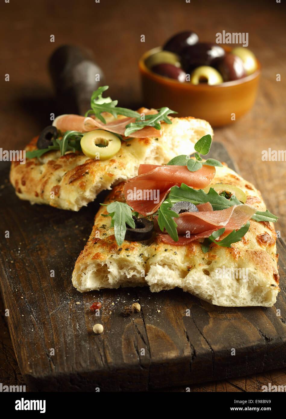 Köstliche traditionelle überbackene italienische Focaccia-Brot mit Schinken, Rucola und Oliven auf alten Stockbild