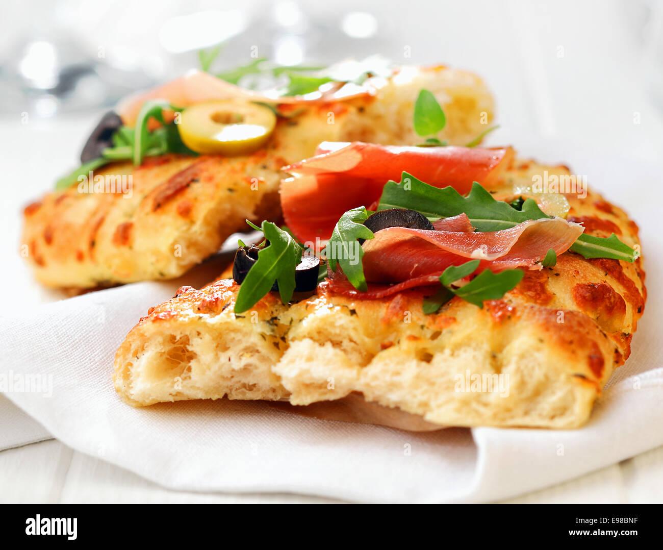 Leckere frisch gebackene traditionelle italienische Focaccia-Brot mit Schinken, Oliven und Rucola auf eine weiße Stockbild