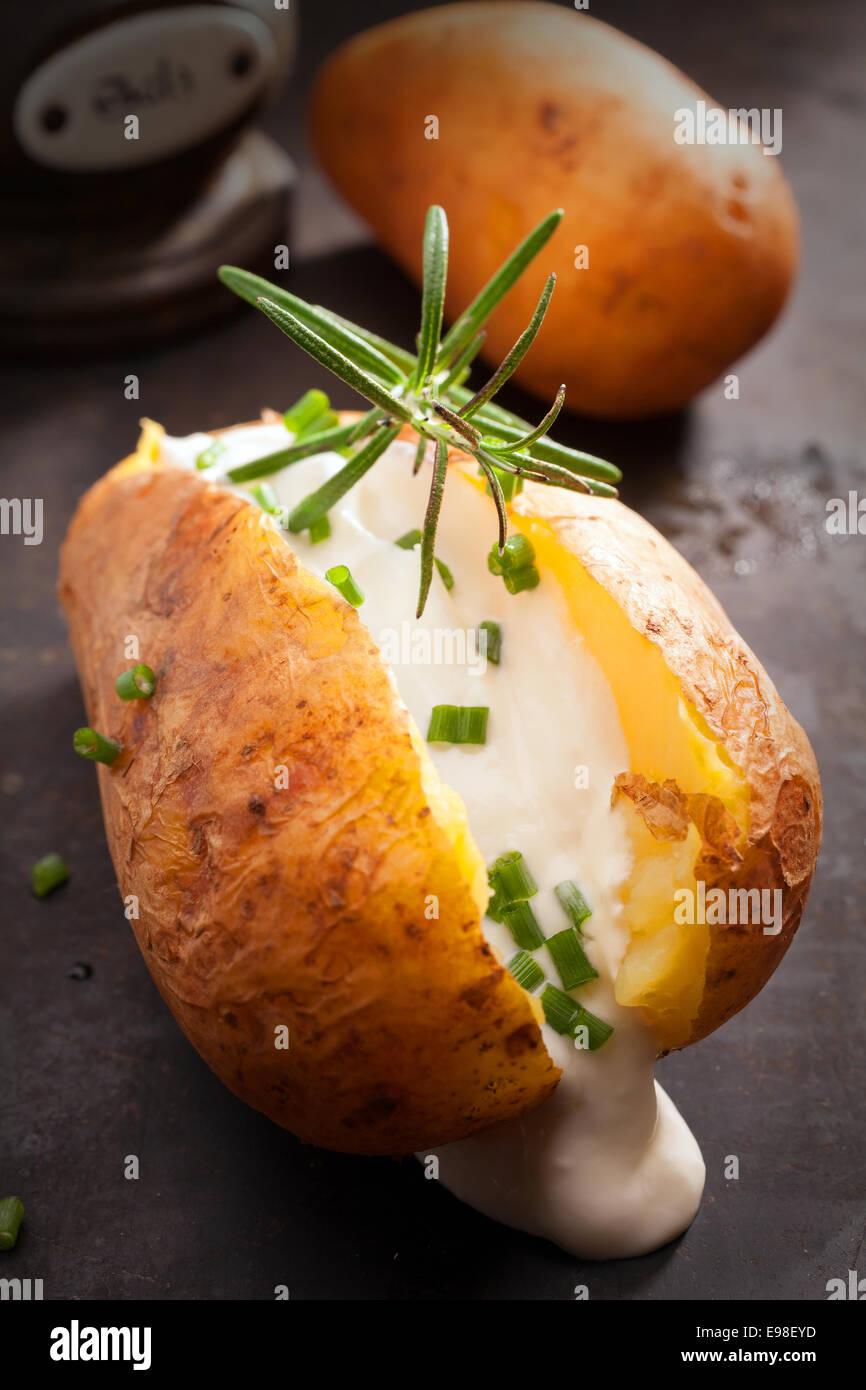 Gebackene Ofenkartoffeln über einen Sommer BBQ in der Folie mit Sauerrahm und Schnittlauch garniert mit Rosmarin Stockbild
