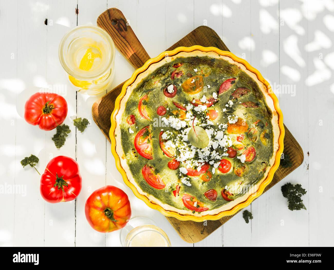 Herzhafte Quiche mit Ei, Tomaten, Käse und Kräutern auf ein Schneidbrett aus Holz mit frischen Tomaten Stockbild