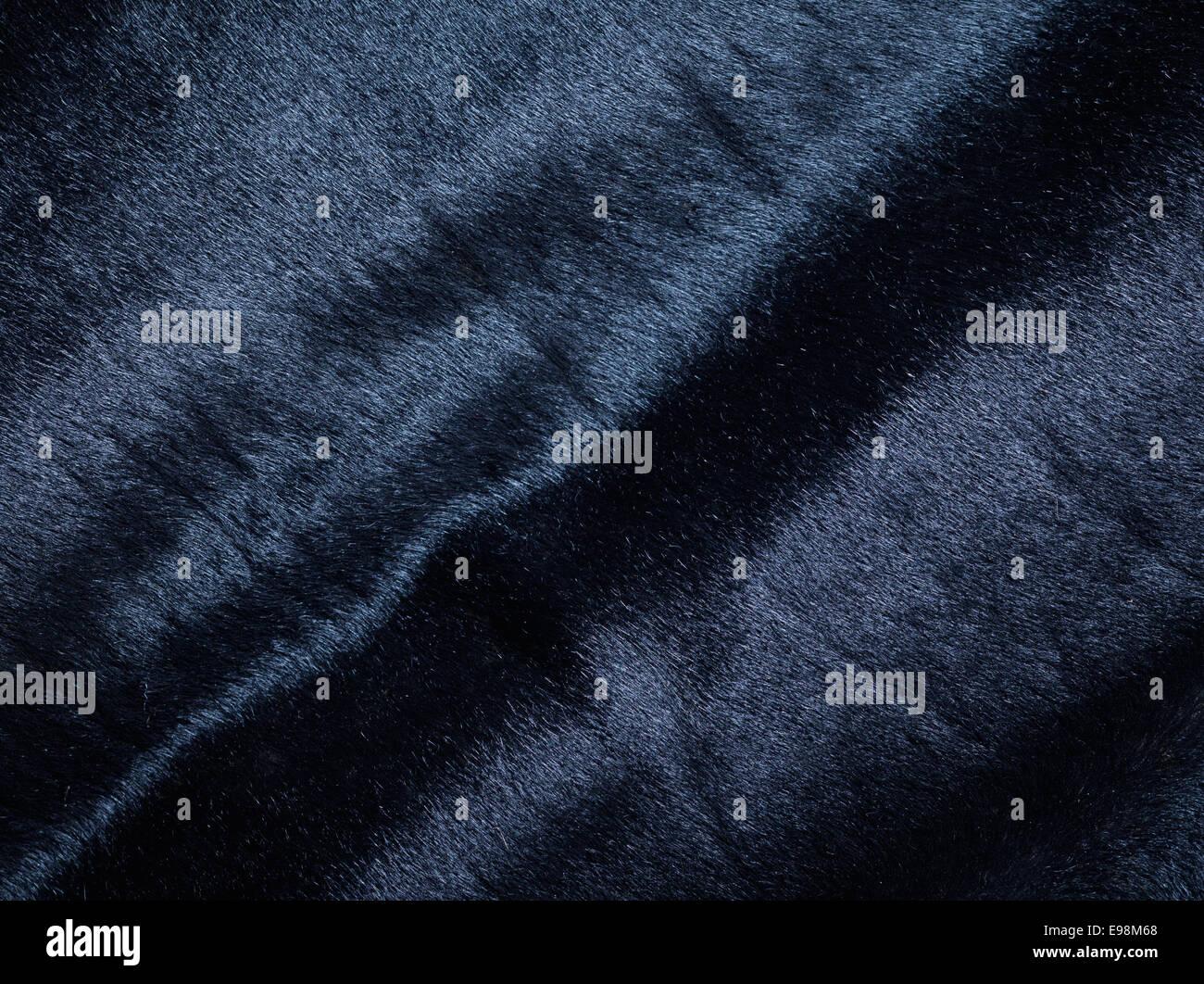 Hintergrund von einem dunklen Stück aus geschmeidigem Wildleder Leder mit Falten Stockbild