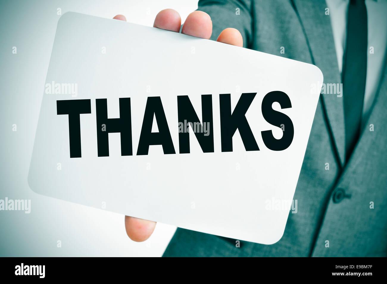 ein Mann in einem Anzug zeigt ein Schild mit dem Wort dank geschrieben Stockbild