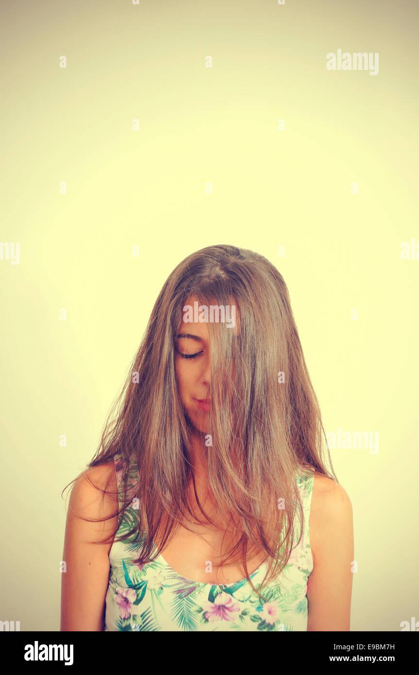 Porträt einer jungen Brünette Frau mit ihrem Haar in ihr Gesicht und ihre Augen geschlossen, mit einem Stockbild