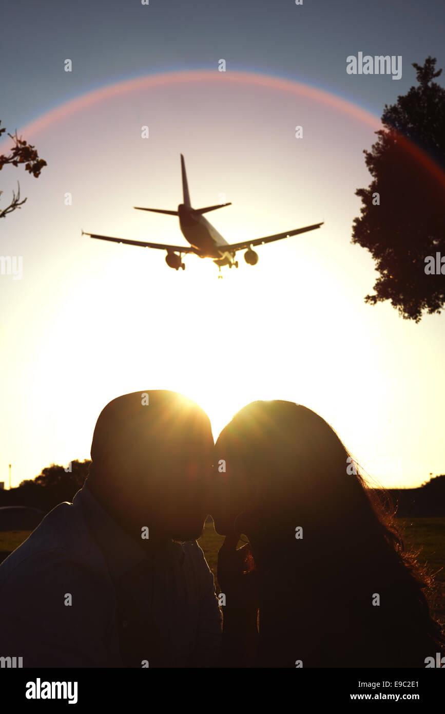 Paar mit Sonne hinter sich und ein Flugzeug fliegen overhead küssen Stockbild