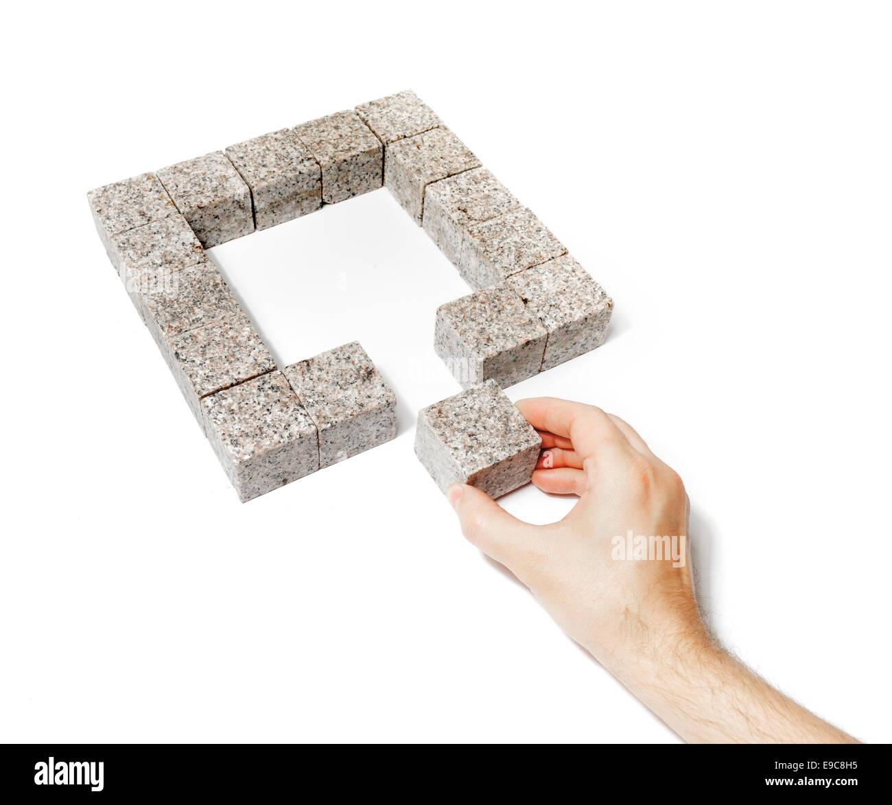 Mann beenden ein Quadrat von kleinen Blöcken von Granitfelsen gemacht. Stockbild