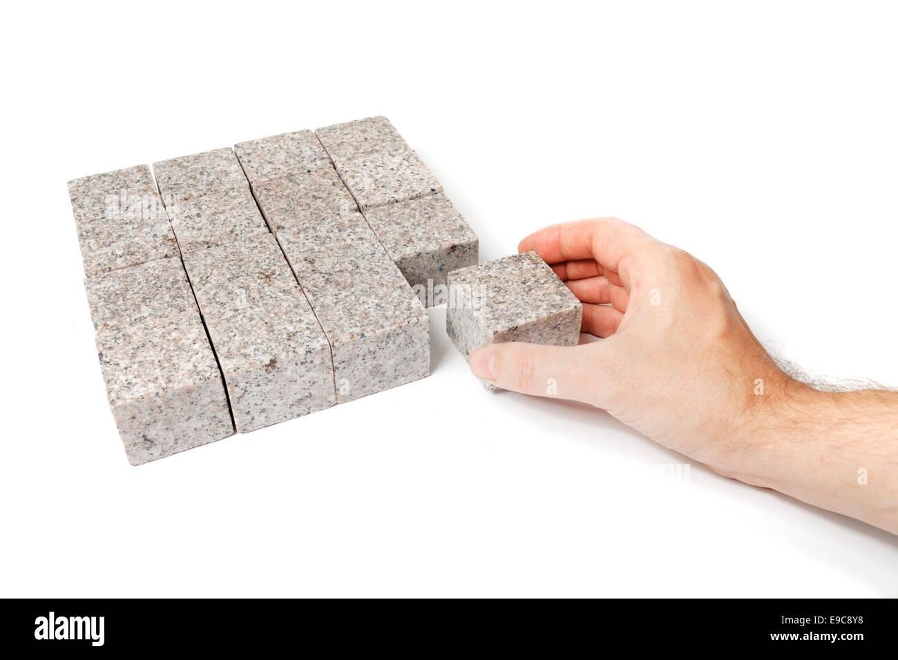 Mann, der eine quadratische Form der Blöcke aus Granitstein. Stockbild