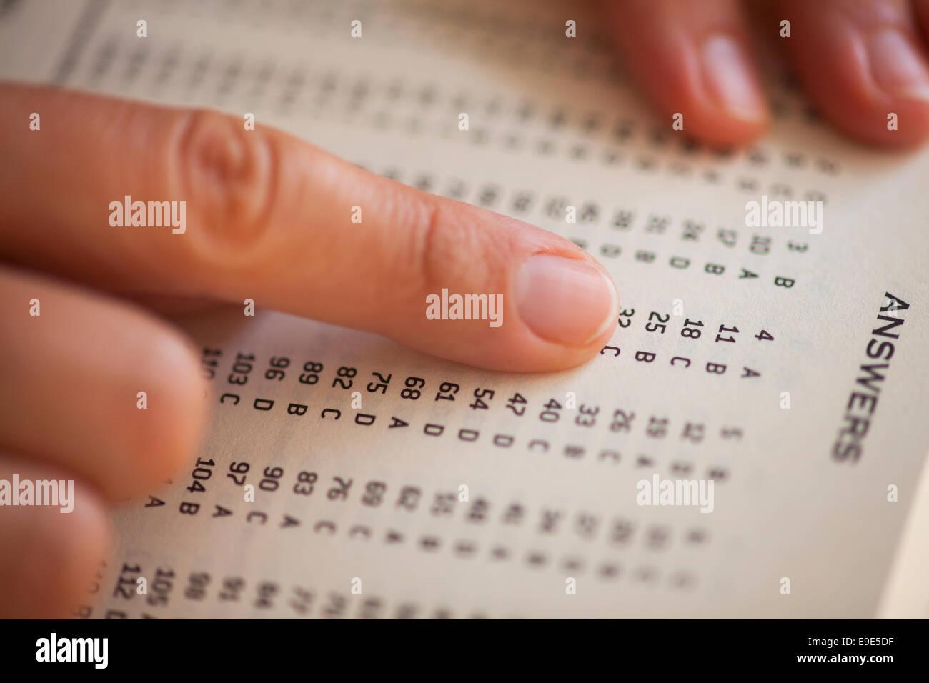 Die Hände der Frau auf Buchseite mit richtigen Antworten. Geringe Schärfentiefe. Stockbild