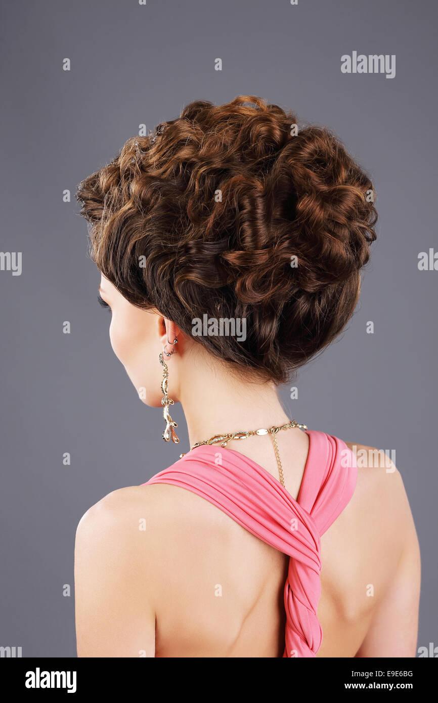Krauses Haar. Rückansicht des braunen Haaren Frau mit festlichen Frisur Stockbild