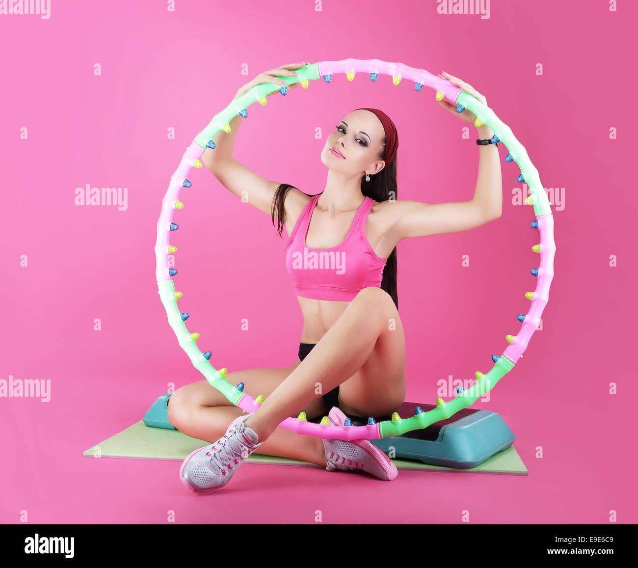 Wellness. Sportclub. Frau sitzt mit Sportgeräten Stockbild