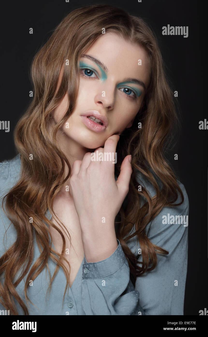Fantasie. Junge Brünette mit ungewöhnlichen blauen Augen Make-up Stockbild