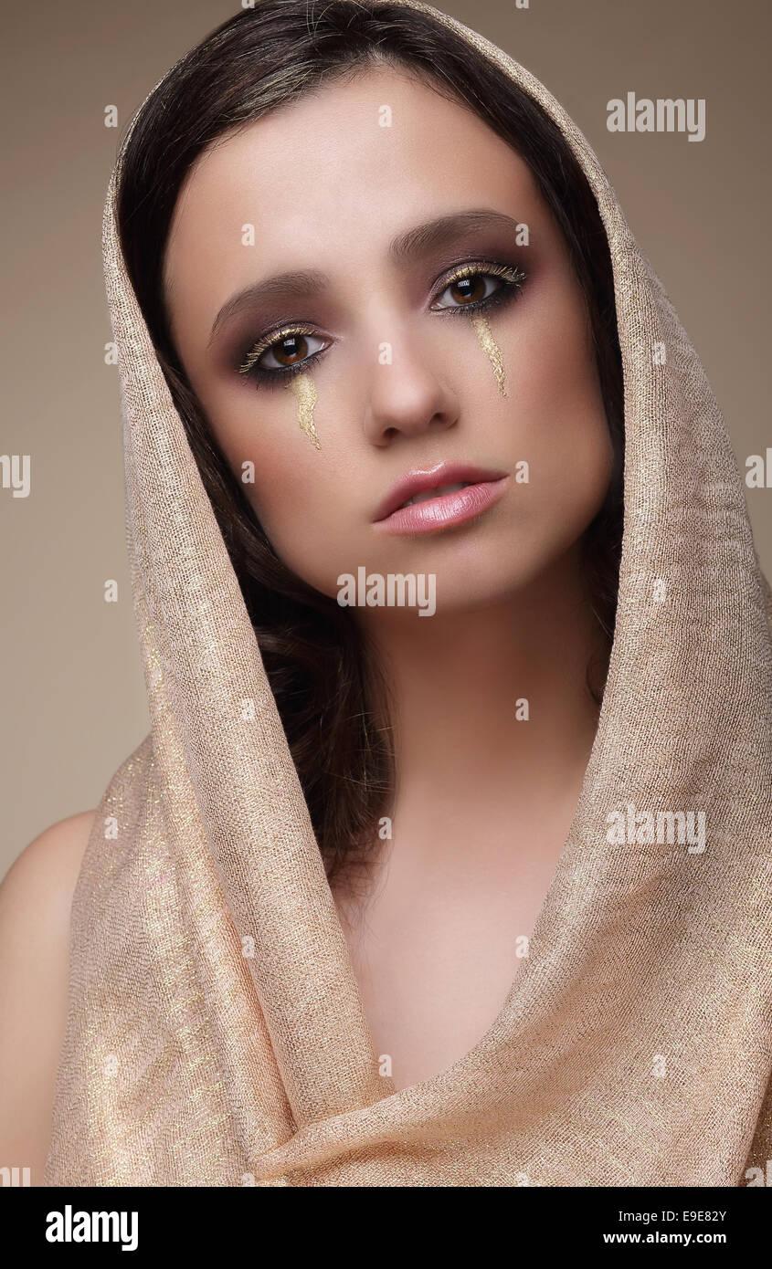Frau in Schal mit dramatischen theatralisch Make-up Stockbild