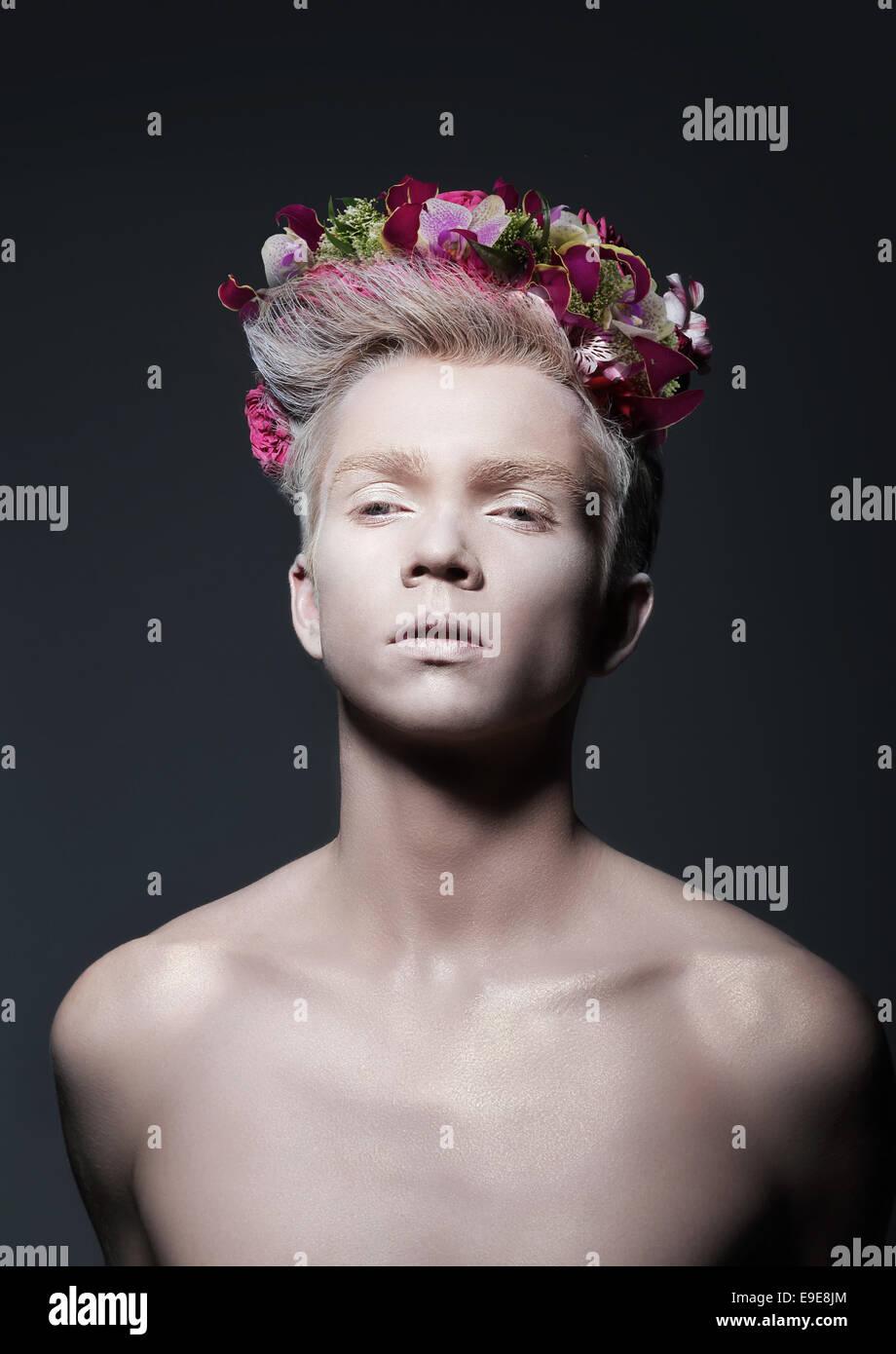 Schönheit. Junger Mann mit Kranz aus Blumen in grau Stockfoto