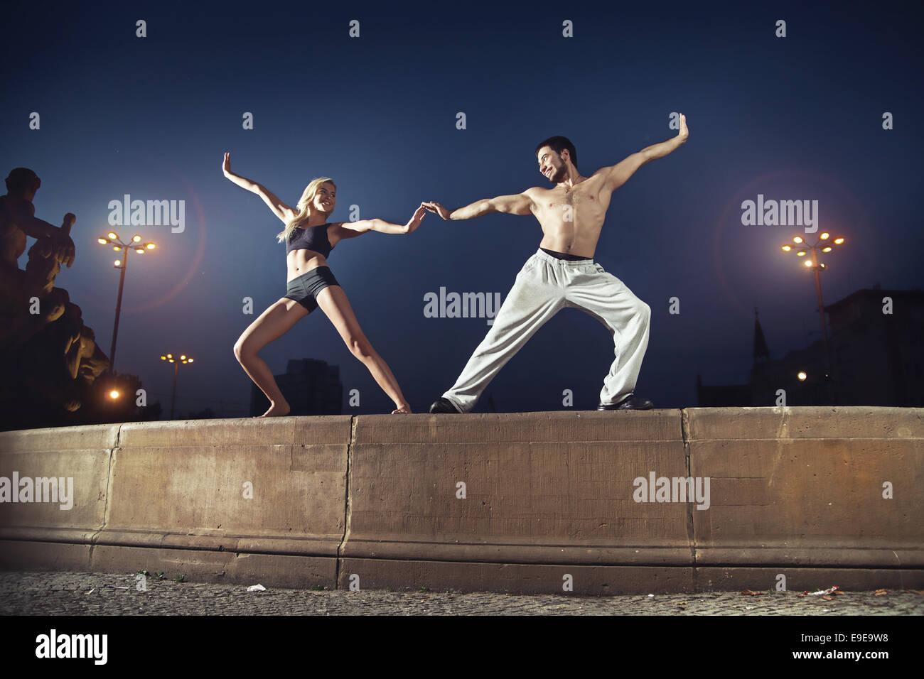 Zwei fröhliche Sportler üben in der Nacht Stockbild