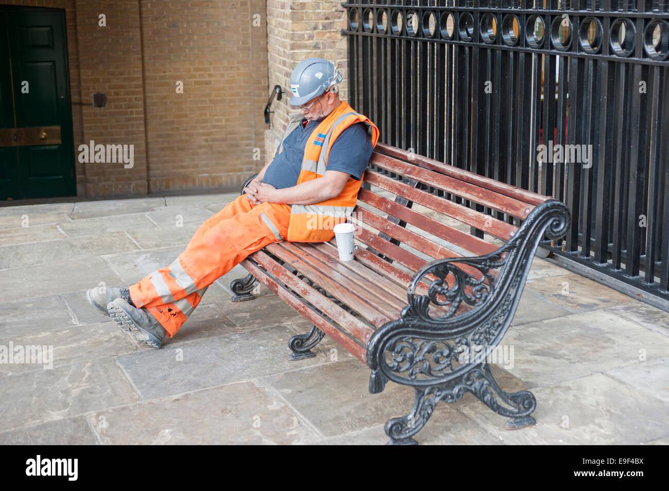 Ein Bauarbeiter mit einem Nickerchen, London, UK Stockbild