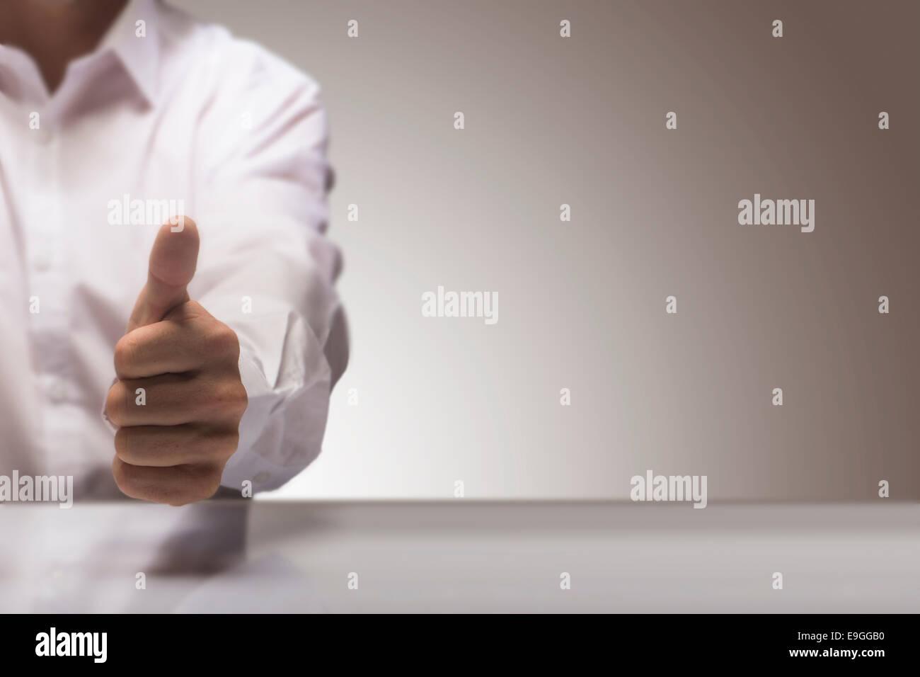 Mann mit einem Daumen oben auf den Hintergrund eines glänzenden Tisch und Kopie Raum auf dem rechten, Konzept Stockbild