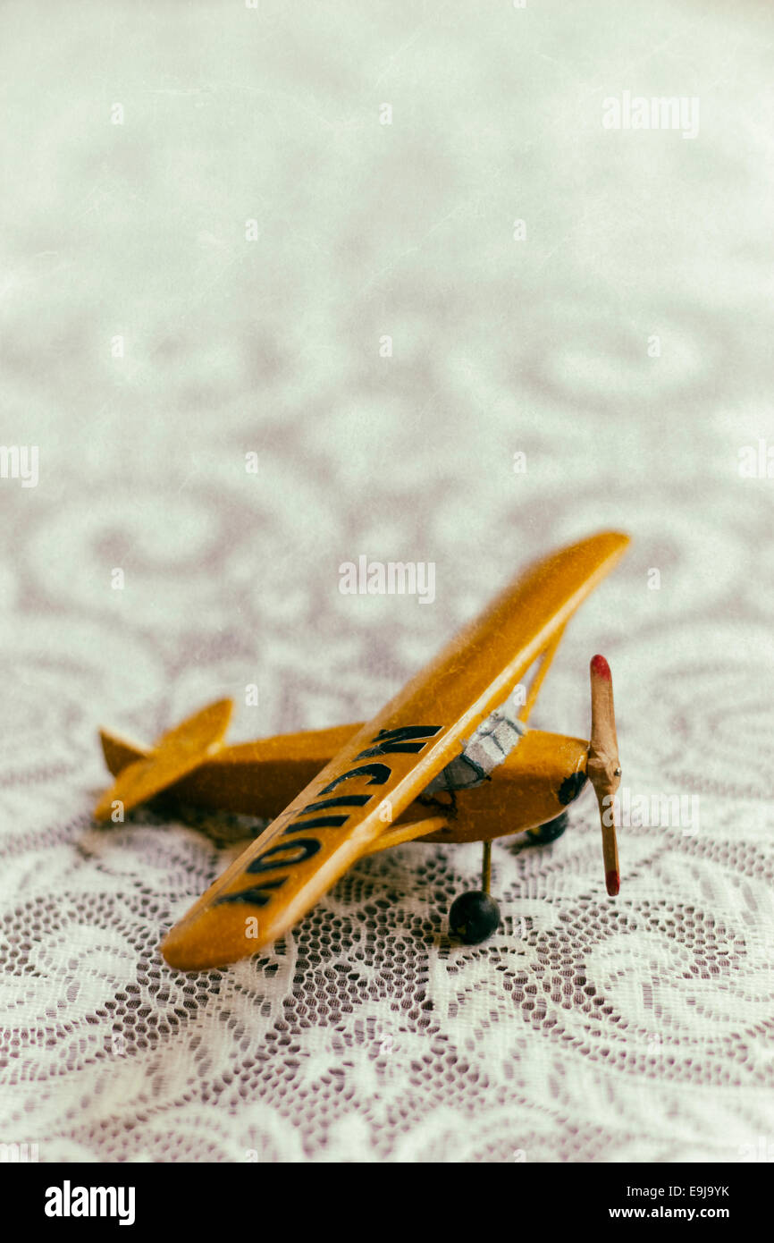 Antike gelbe hölzernes Spielzeugflugzeug sitzt auf einer Tischplatte Spitze überzogen. Stockbild