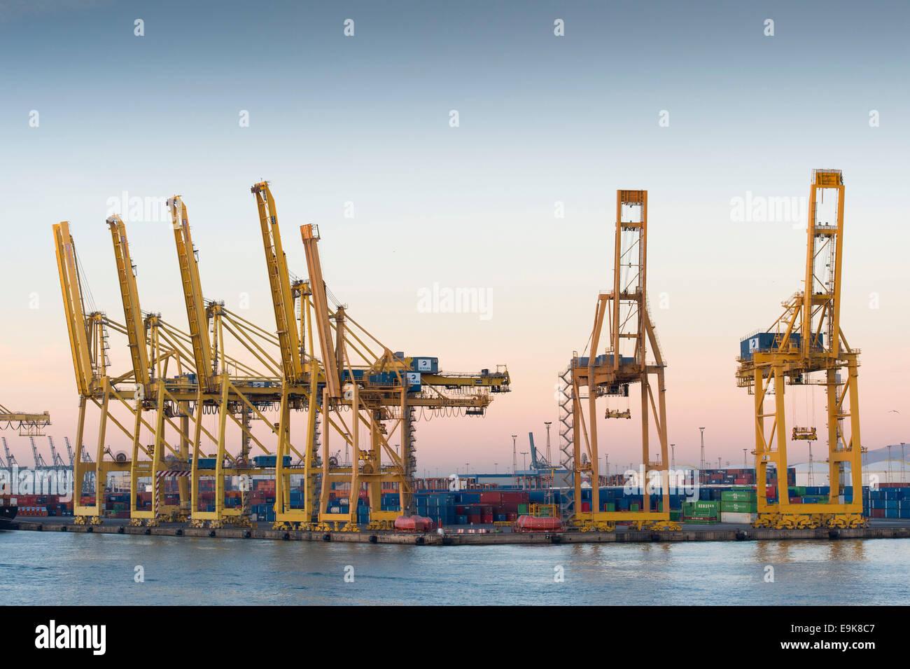 Gelben Kräne bewegen Versandbehälter an Barcelonas Hafen - Port de Barcelona - bei Sonnenaufgang. Stockbild