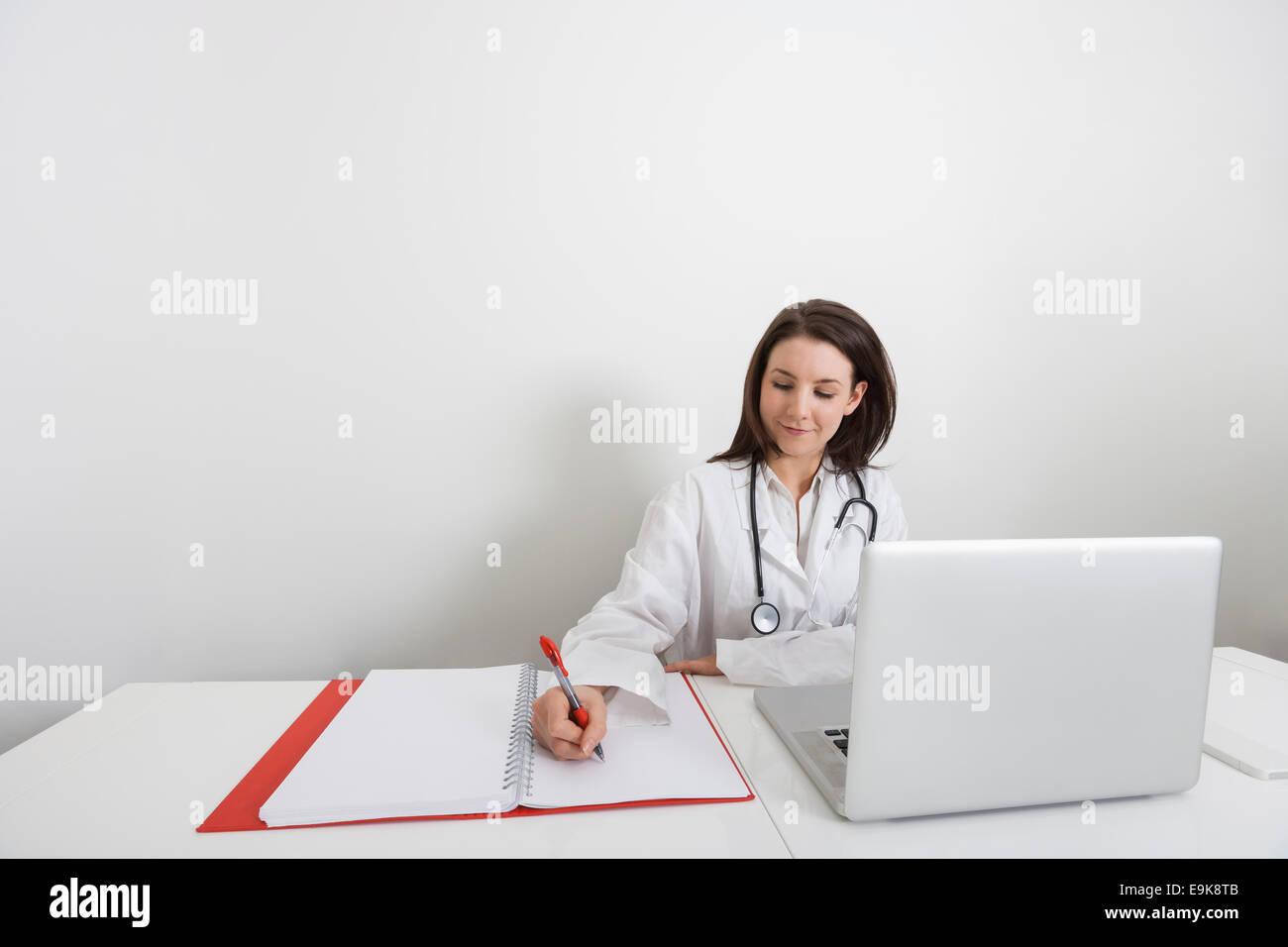 Ärztin, schreiben auf Binder auf Schreibtisch in Klinik Stockbild